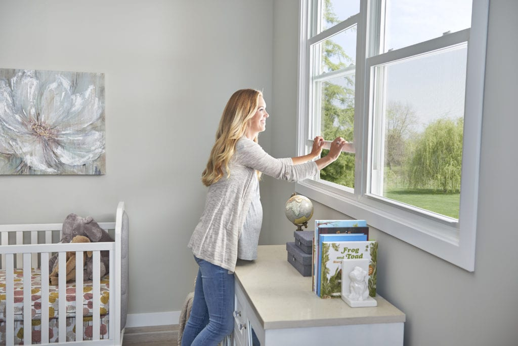 A smiling pregnant blonde woman in a nursery, reaching over a dresser to easily lower a window.