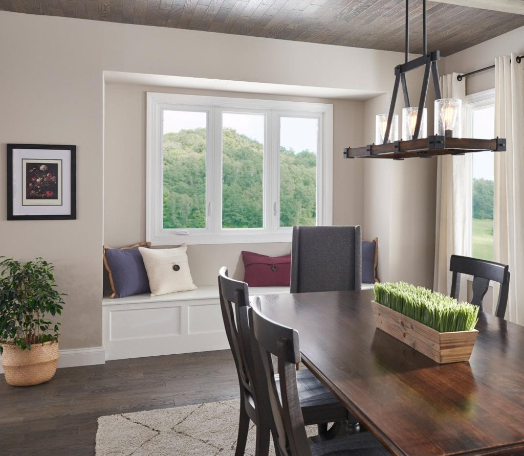 A stylish dining room with a dark wood table, farmhouse overhead light fixture and window seat with pillows.