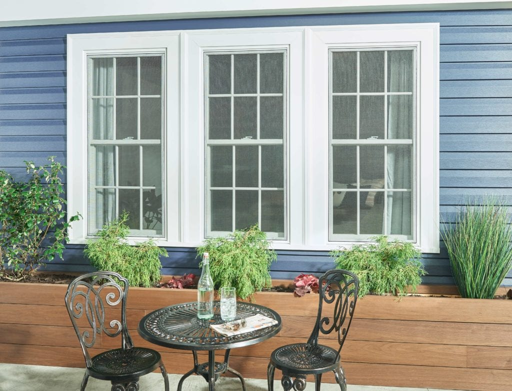 A wrought iron outdoor patio set placed in front of a blue house with white windows and landscaping.