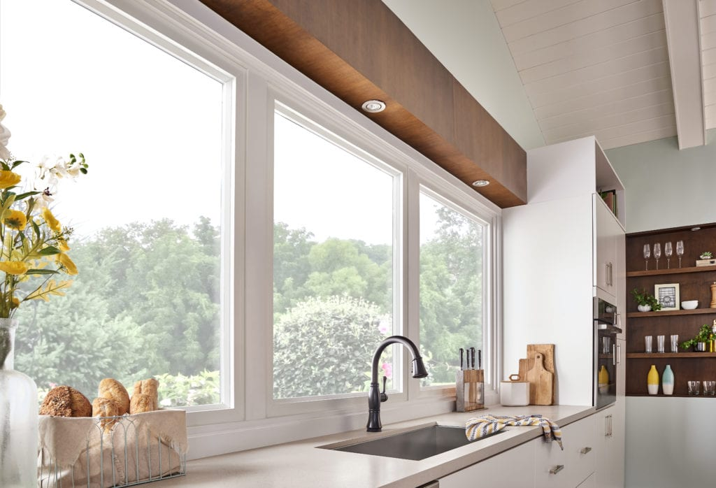 A clean white kitchen with three large windows behind a single-basin kitchen sink.