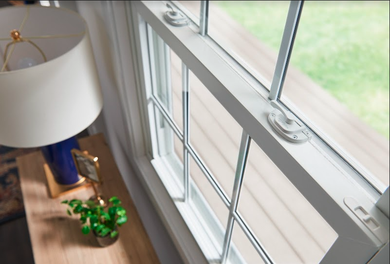 A close up of a white double hung window behind a wooden table with a blue lamp and a plant.