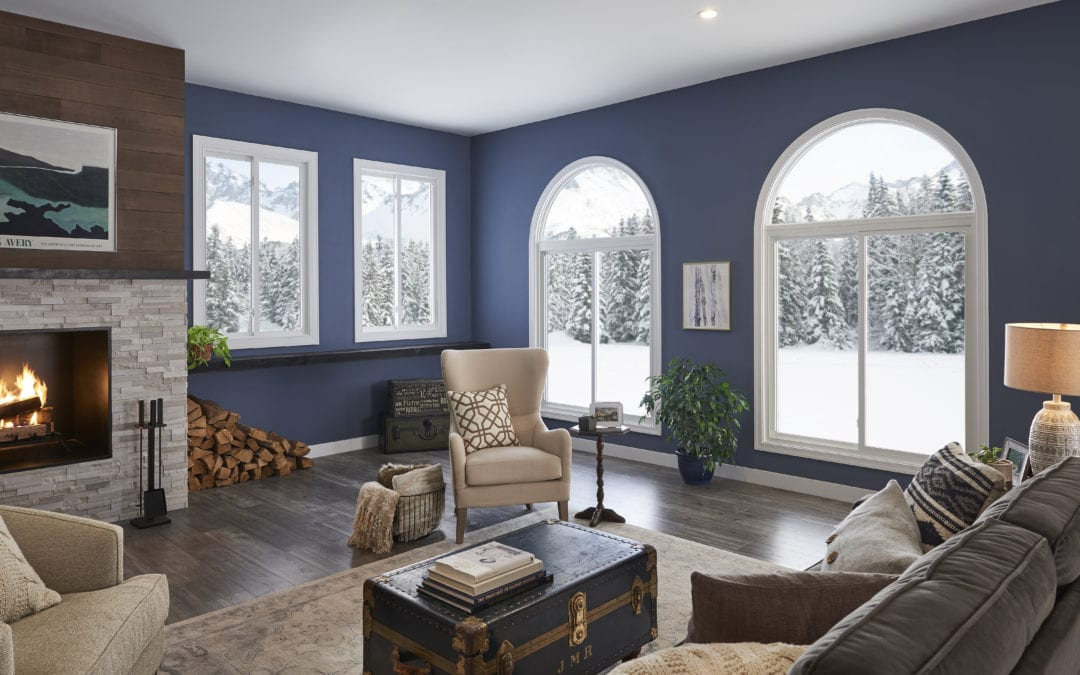 A beautiful living room with blue walls and a fireplace overlooking a snowy landscape.
