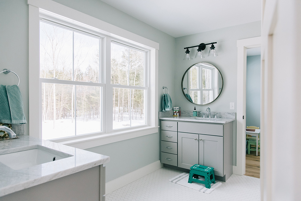 A pale blue bathroom with large double hung white windows overlooking a snowy landscape.