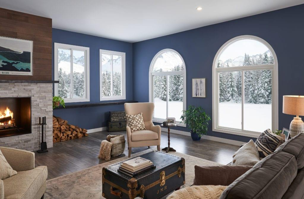 A indigo blue living room with a fireplace, overstuffed couch and comfortable chairs.