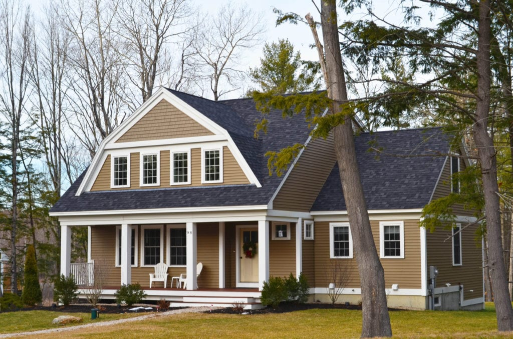 A picturesque home on a wooded lot with light brown siding and contrasting white windows, a wide front porch and dark gray roof.