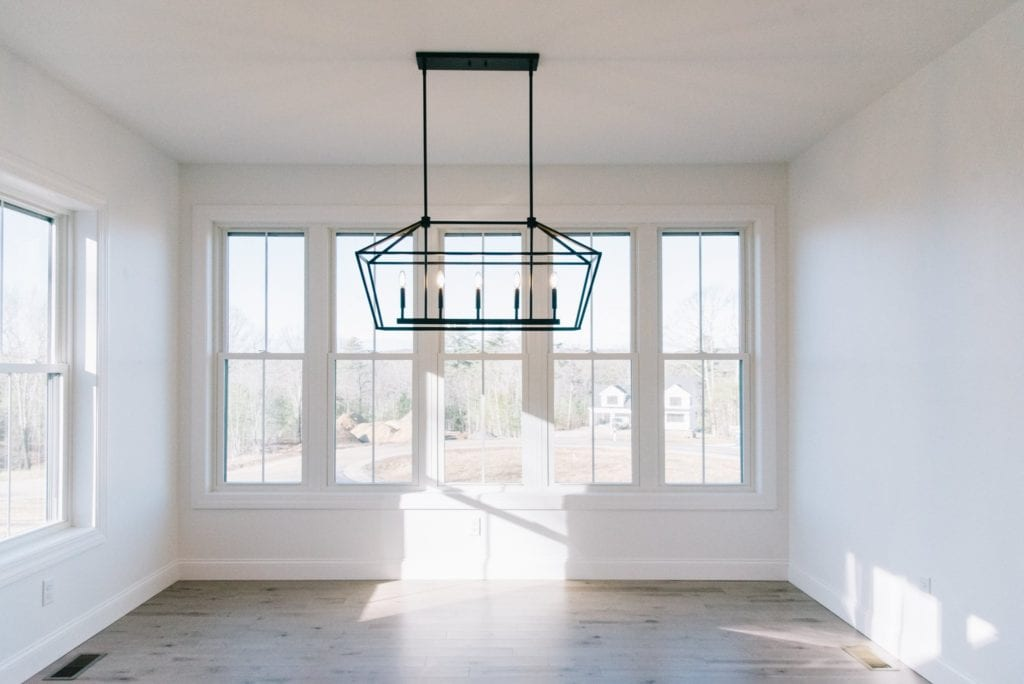 A well-lit empty room with two walls of windows, wood floors and geometrical light fixture.