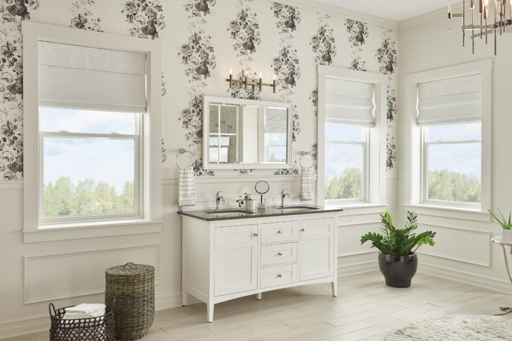 A large shabby chic bathroom with floral patterned wallpaper, a vintage-inspired bathroom cabinet and large windows overlooking the forest.