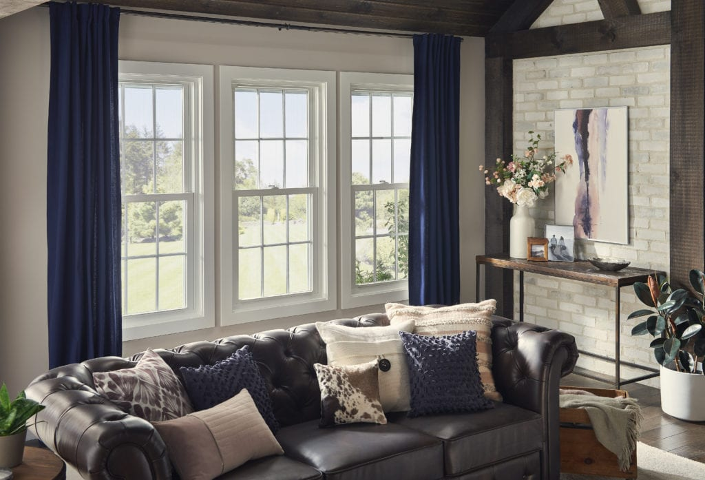 A well-designed living room with three large windows, dark blue curtains and a homey leather couch with large, inviting accent pillows.