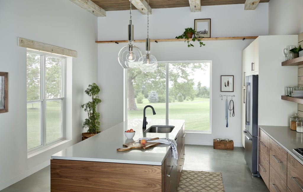 A well-lit kitchen with white walls, wooden cabinets and concrete floors