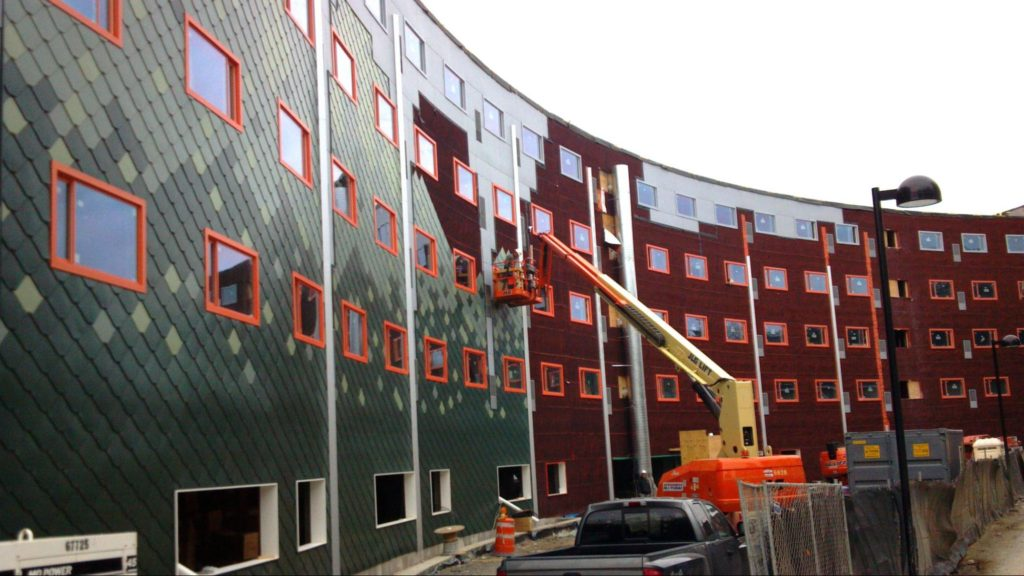 A side view of a commercial building as green cladding is installed, complementing the orange-framed Paradigm windows.