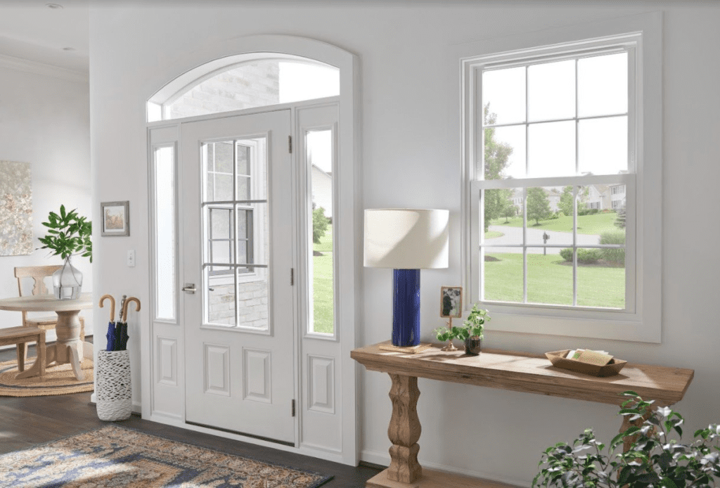 View of a white front door and entry windows from inside the home surrounded by wood flooring, colorful rug and greenery