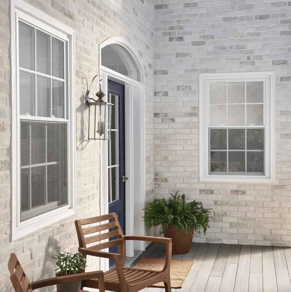White and grey toned brick home exterior with a dark blue door, two windows and outdoor chairs.