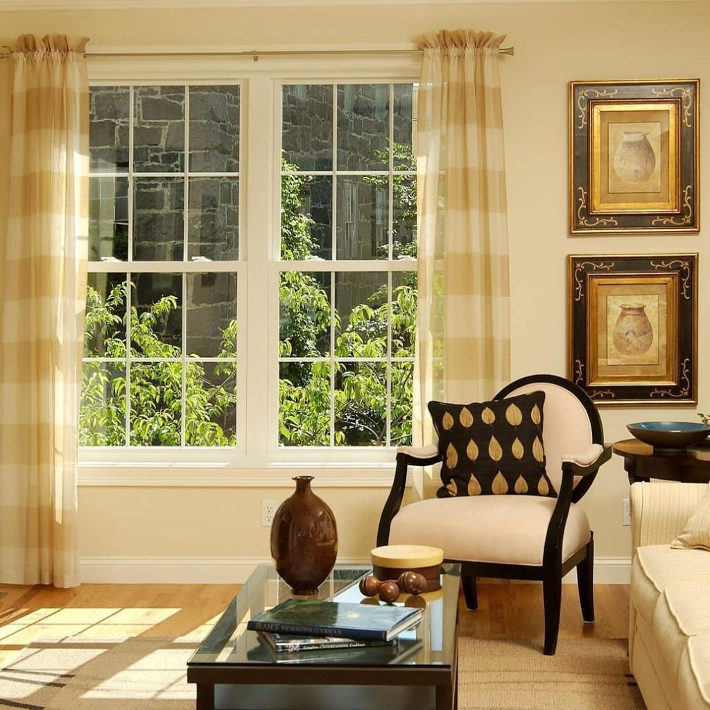 Living room with two large traditional styled windows, two hanging pictures, striped curtains and black and gold pillow laying on a white and black chair.